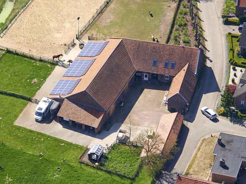 Blick auf landwirtschaftliches Gebäude mit Photovoltaik aus der Luft